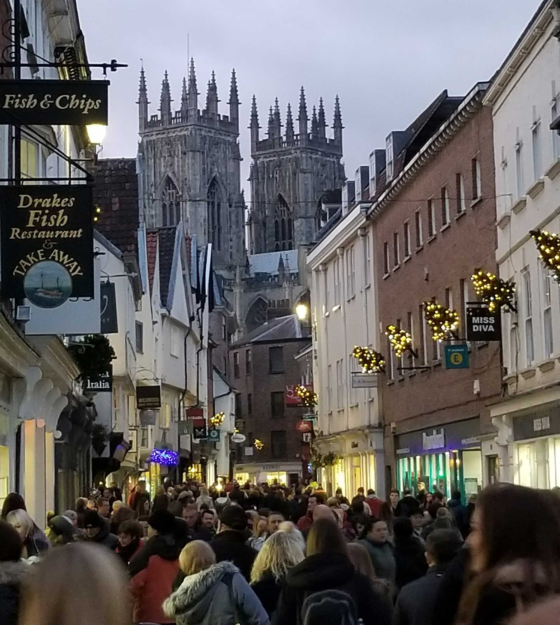 Christmas shoppers pictured with a backdrop of York Minster