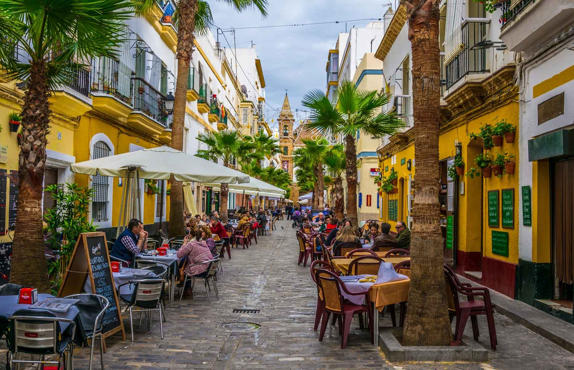 Yellow buildings and palm trees of Cadiz cafe and restaurant street
