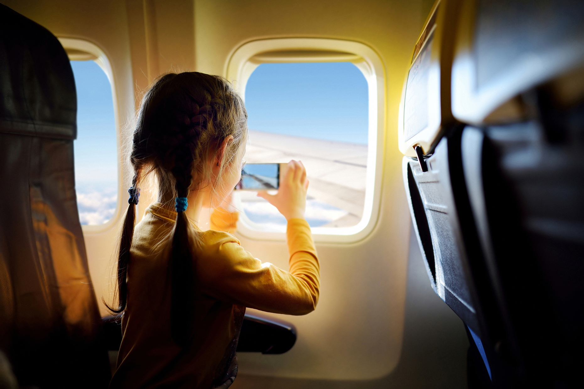Girl taking pictures on a plane