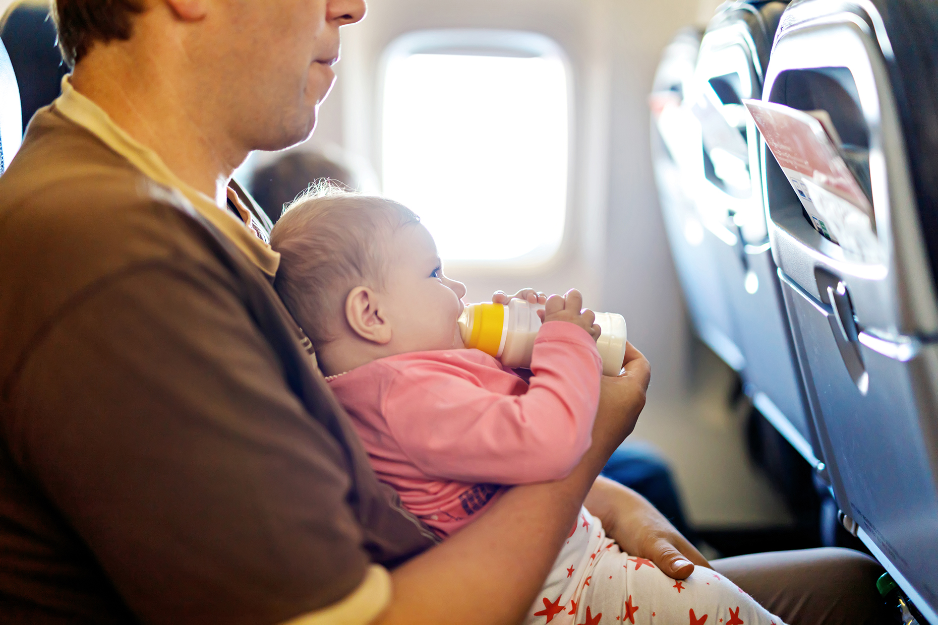 Father holding baby on a plane