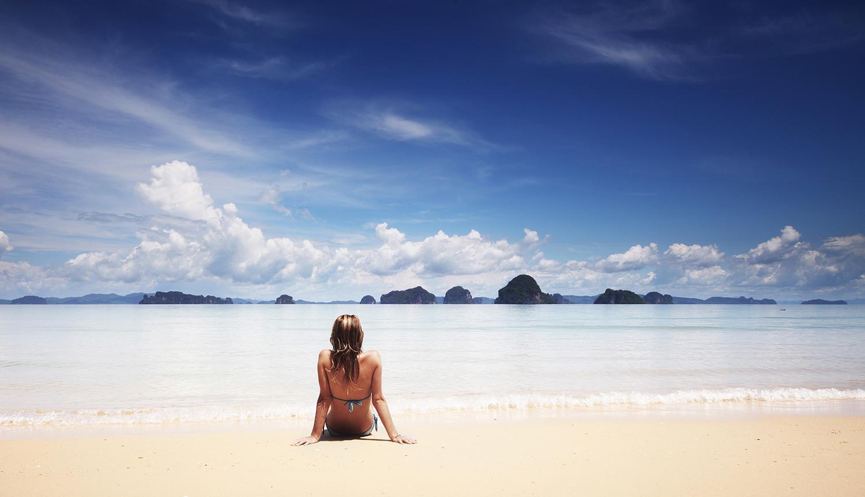 Woman on beach having digital detox holidays