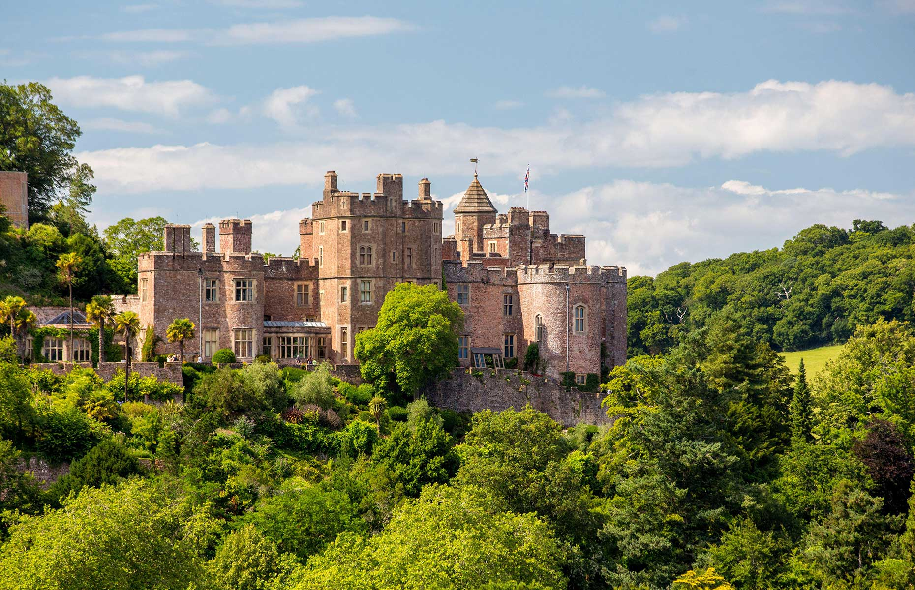 Dunster Castle viewed from a distance in summer with the red brick contrasting against the green trees (Andrew Duke/Alamy Stock Photo)