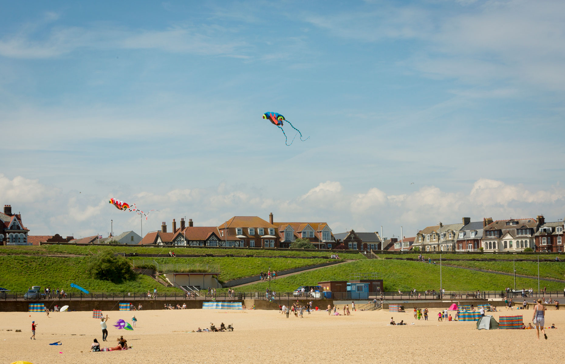Gorleston-on-Sea's golden sandy beach on a sunny day with kites and sunbathers (Image: Visit Great Yarmouth)