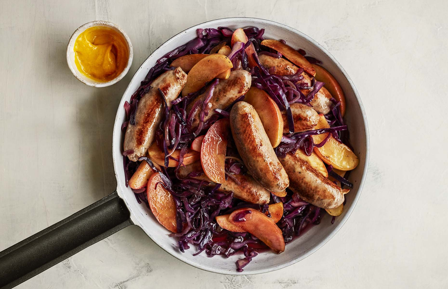 Quick braised red cabbage, sausages and apples (Image: Waitrose & Partners/loveFOOD)