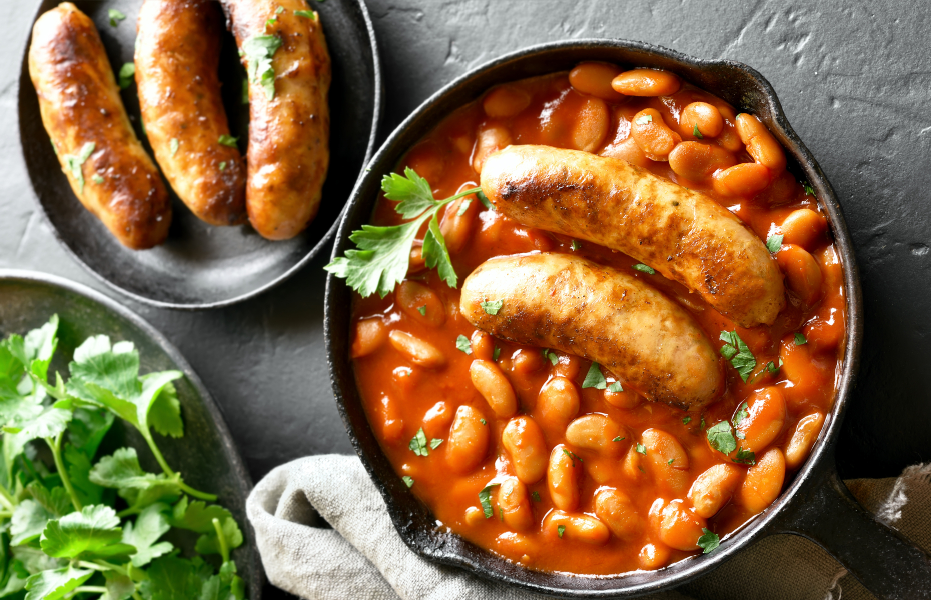 Beans and sausages in a skillet (Image: Tatiana Volgutova/Shutterstock)