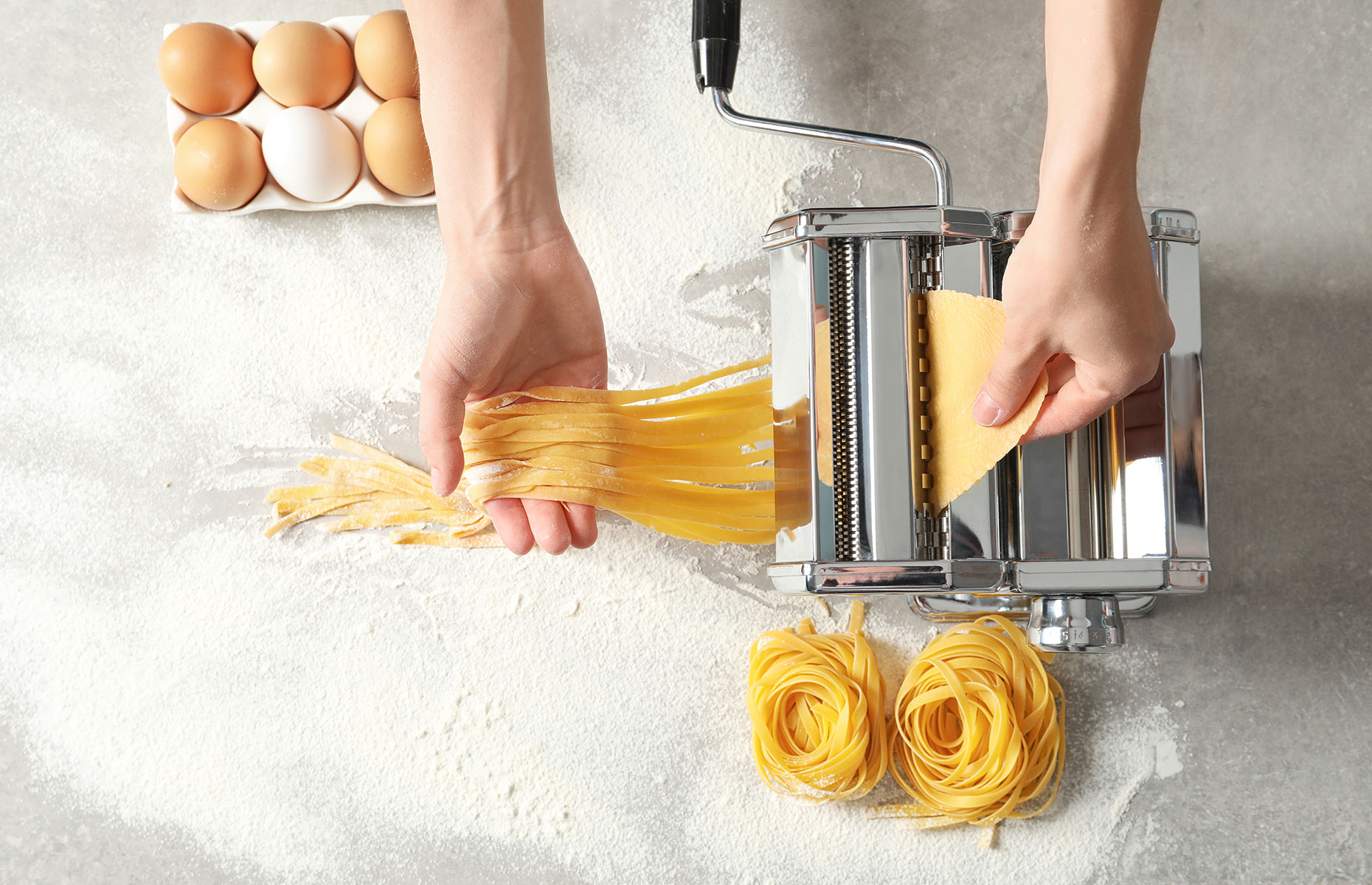 Homemade pasta noodles taking shape in a machine