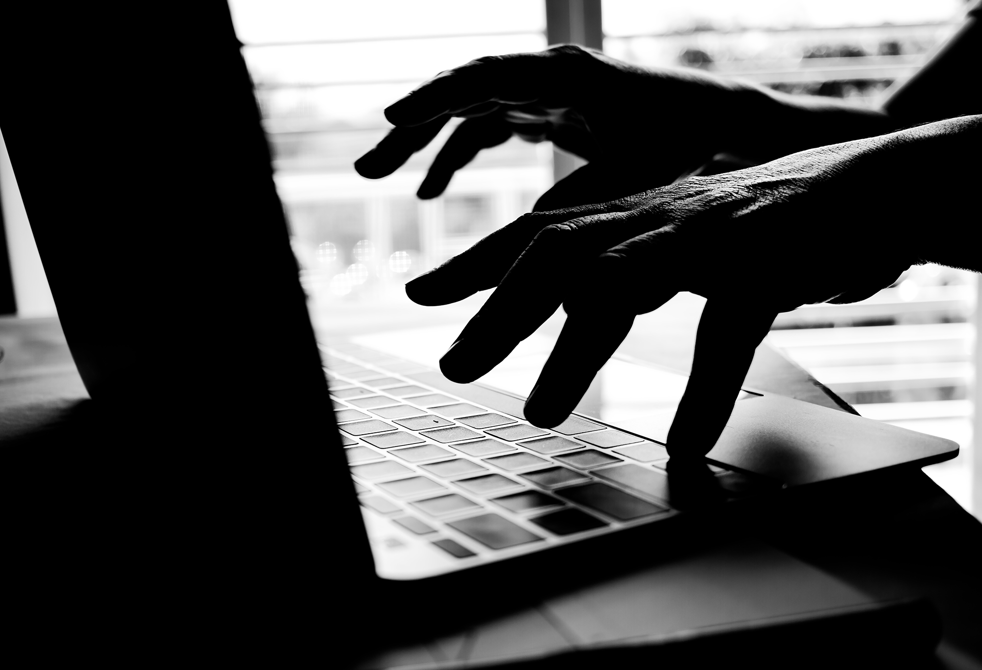 Unknown person using a laptop. (Image: Shutterstock)