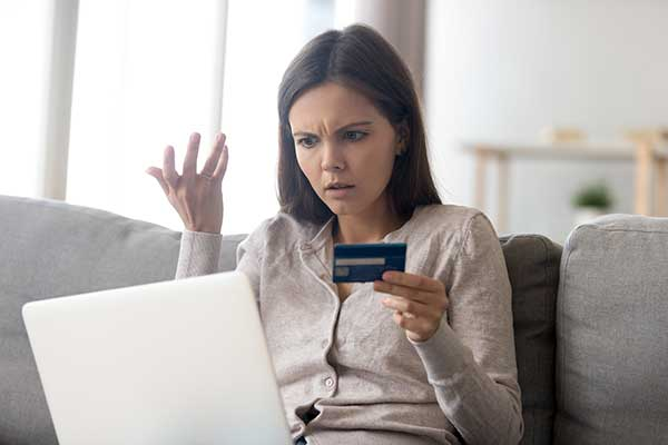 Upset woman looking at a computer. (Image: Shutterstock)