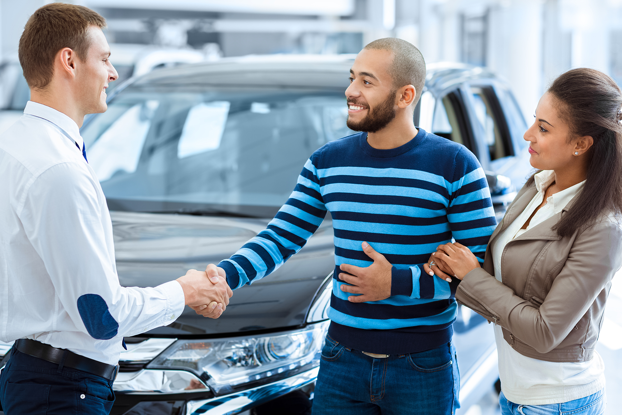 Happy couple shaking hands with a salesman. (Image: Shutterstock)