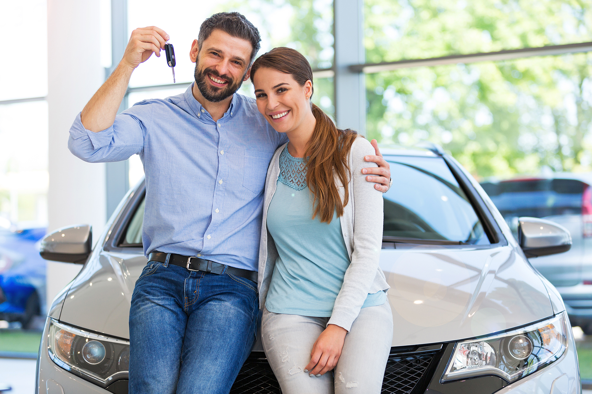 A couple with keys to a new car. (Image: Shutterstock)