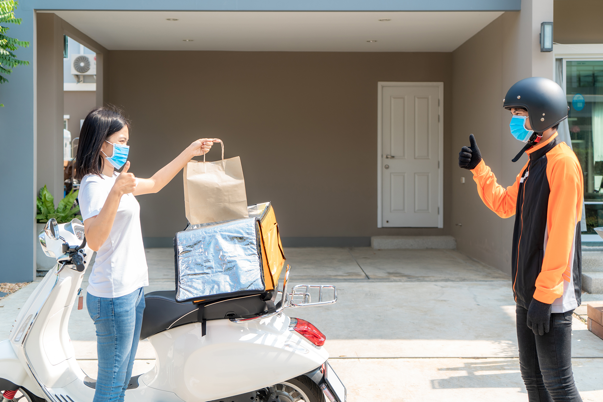 Woman getting takeaway delivered contact-free. (Image: Shutterstock)