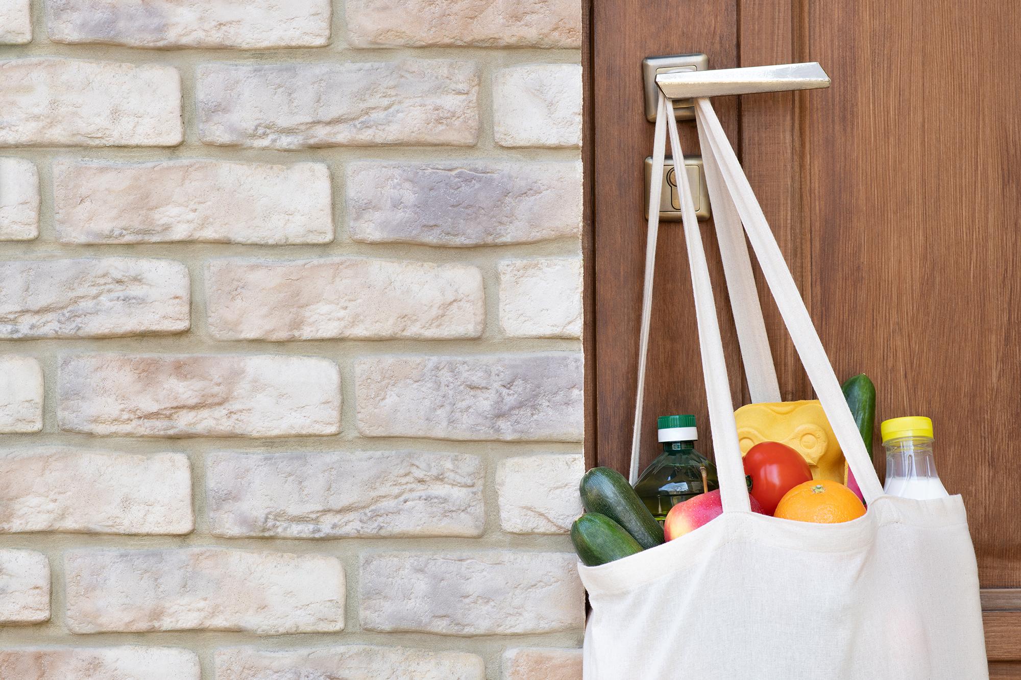 Bag of groceries hanging on doorknob. (Image: Shutterstock)
