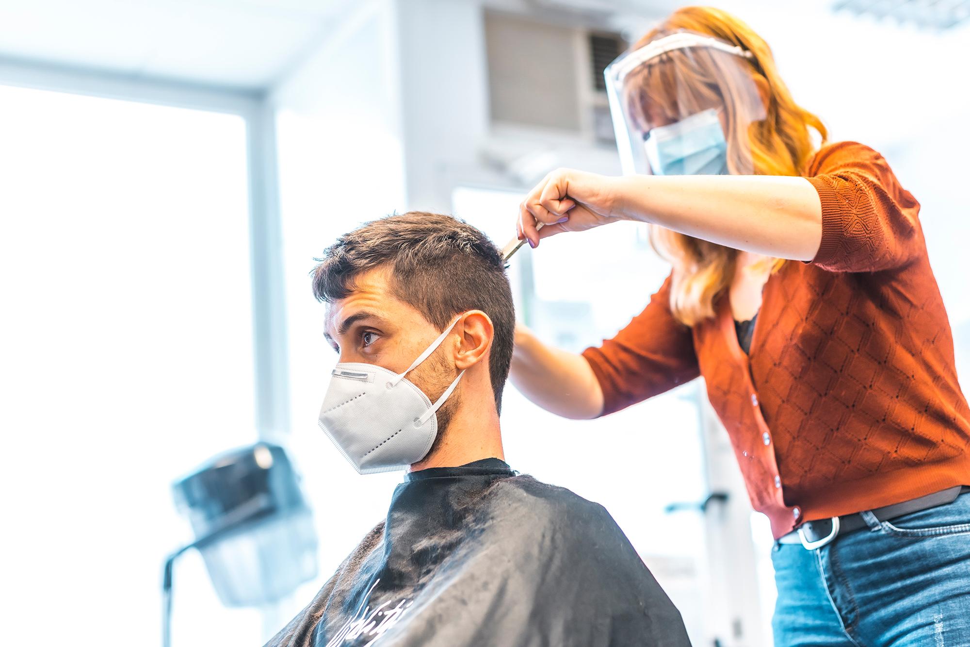 Woman cutting a man's hair. (Image: Shutterstock)