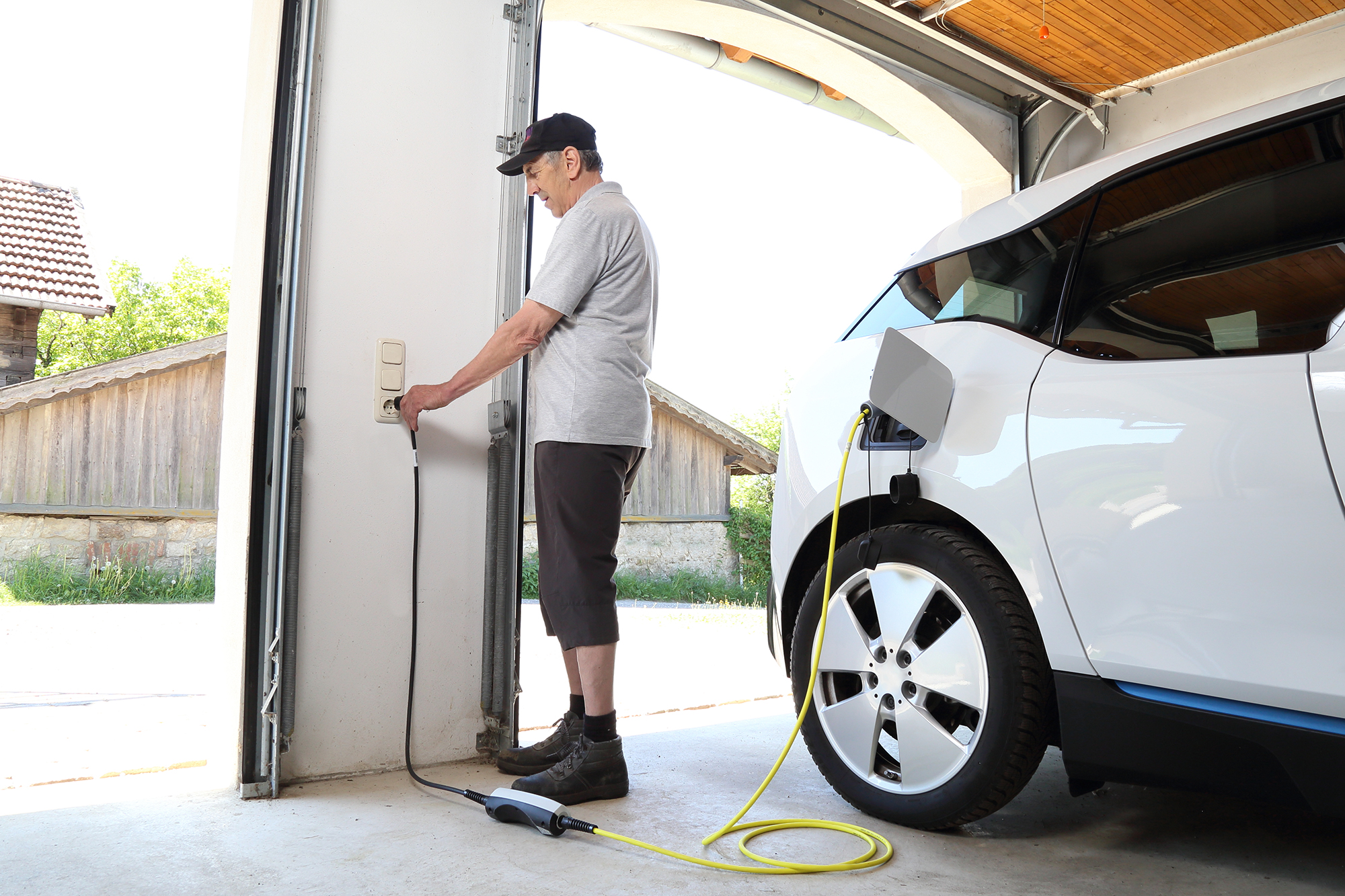 Man charging electric car at home. (Image: Shutterstock)