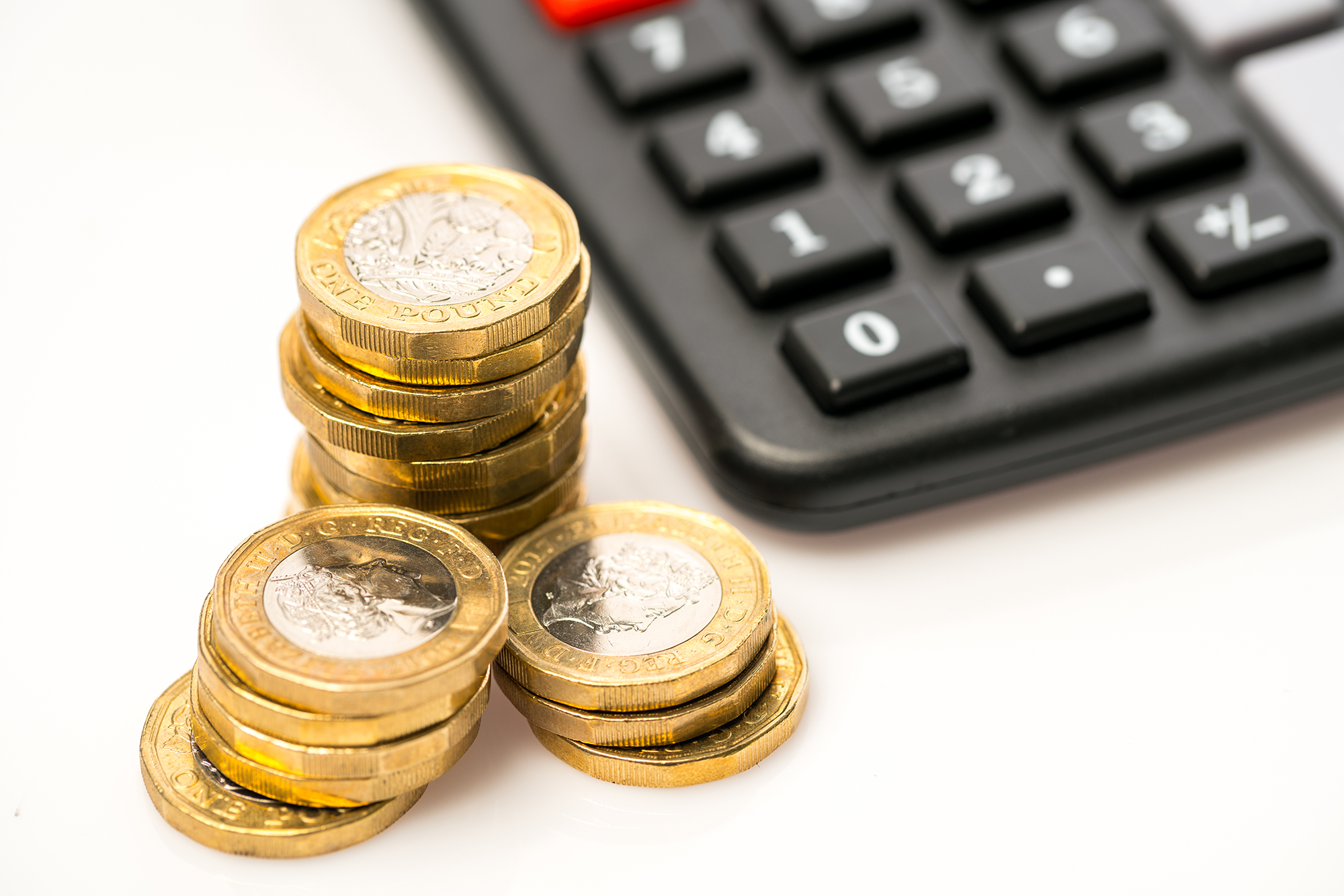 Pound coins next to calculator. (Image: Shutterstock)