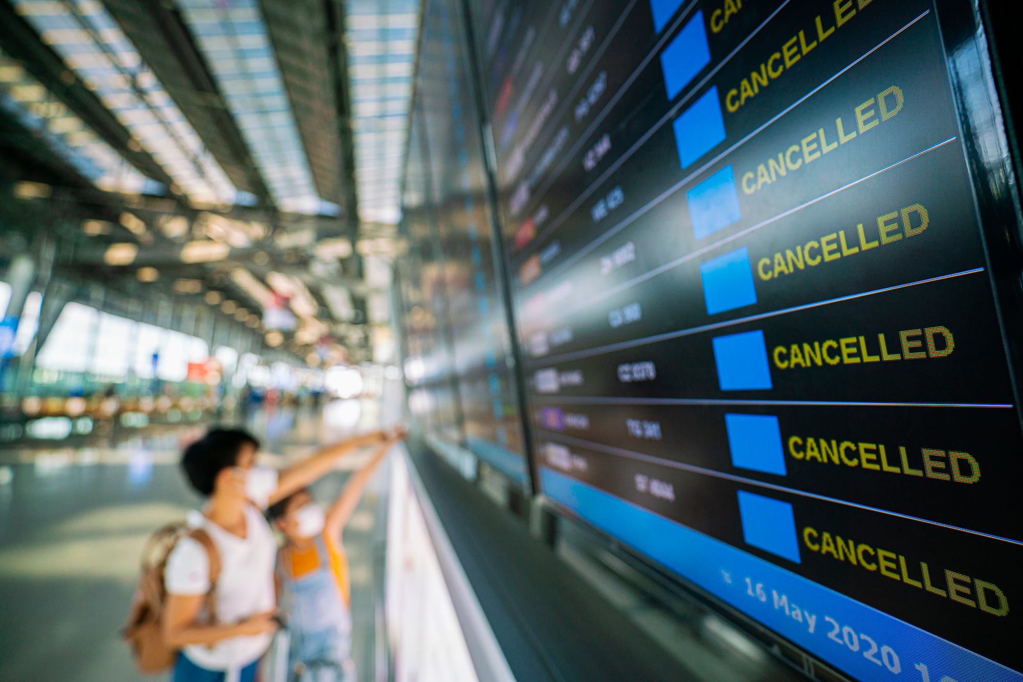 Woman looking at board announcing cancelled flights. (Image: Shutterstock)