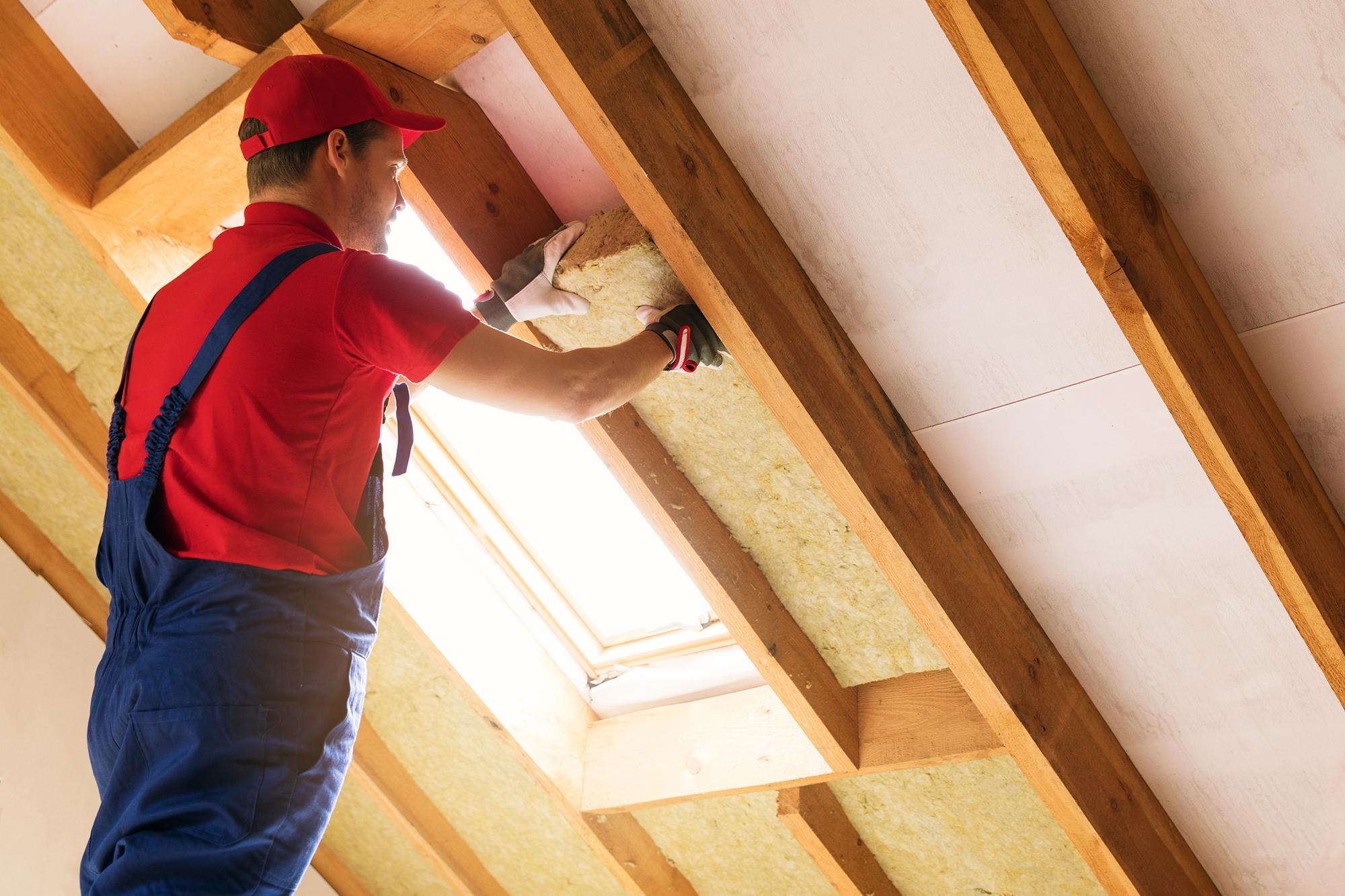 A worker installing insulation. (Image: Shutterstock)
