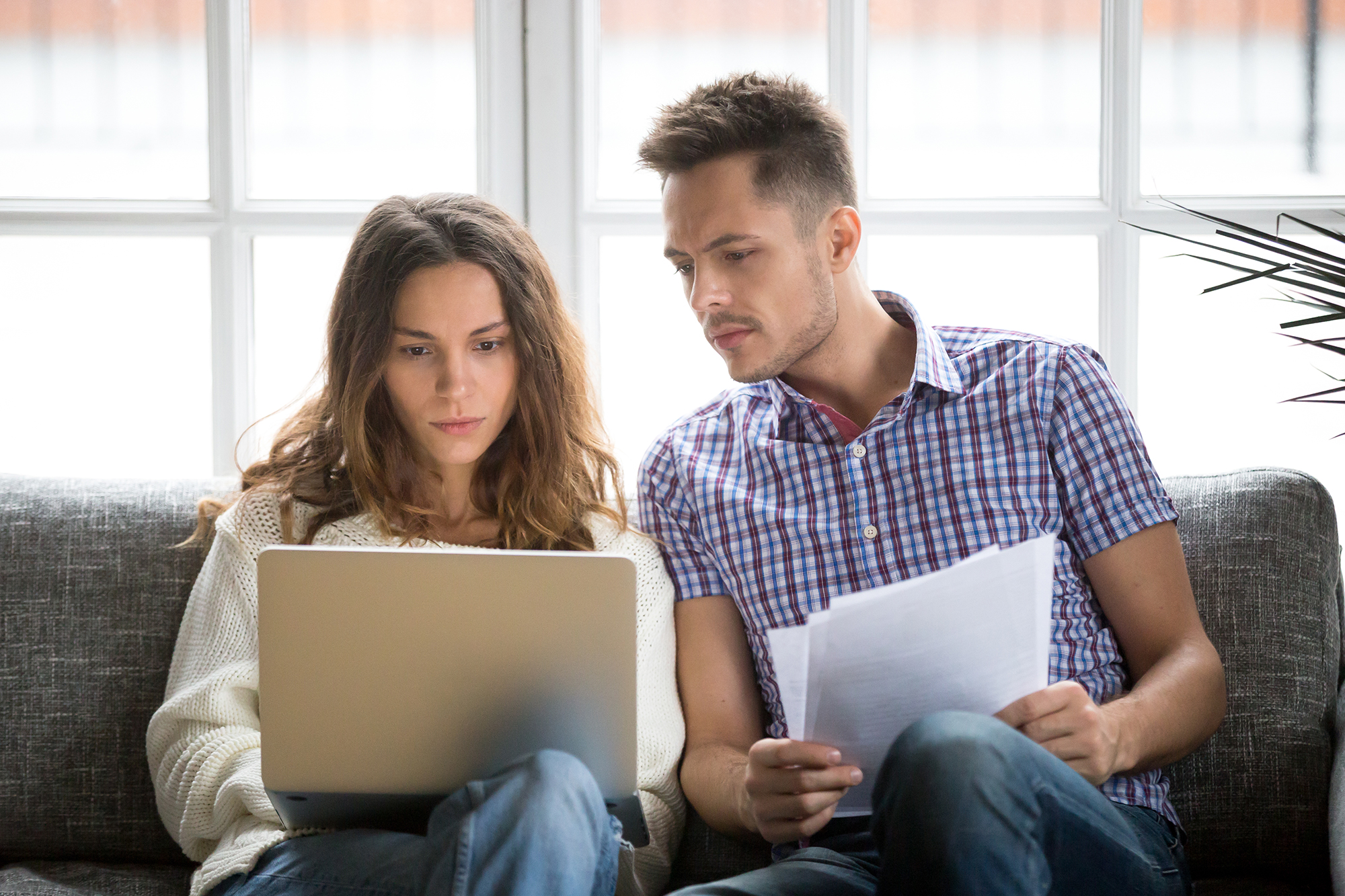 A couple checking an insurance policy. (Image: Shutterstock)