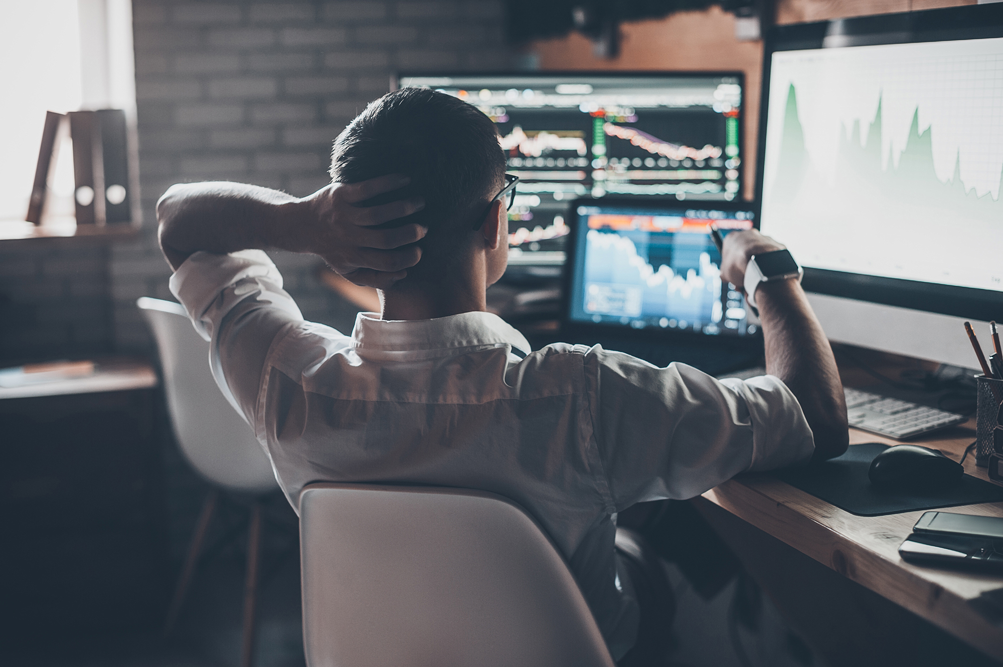 Man at desk looking at investments. (Image: Shutterstock)