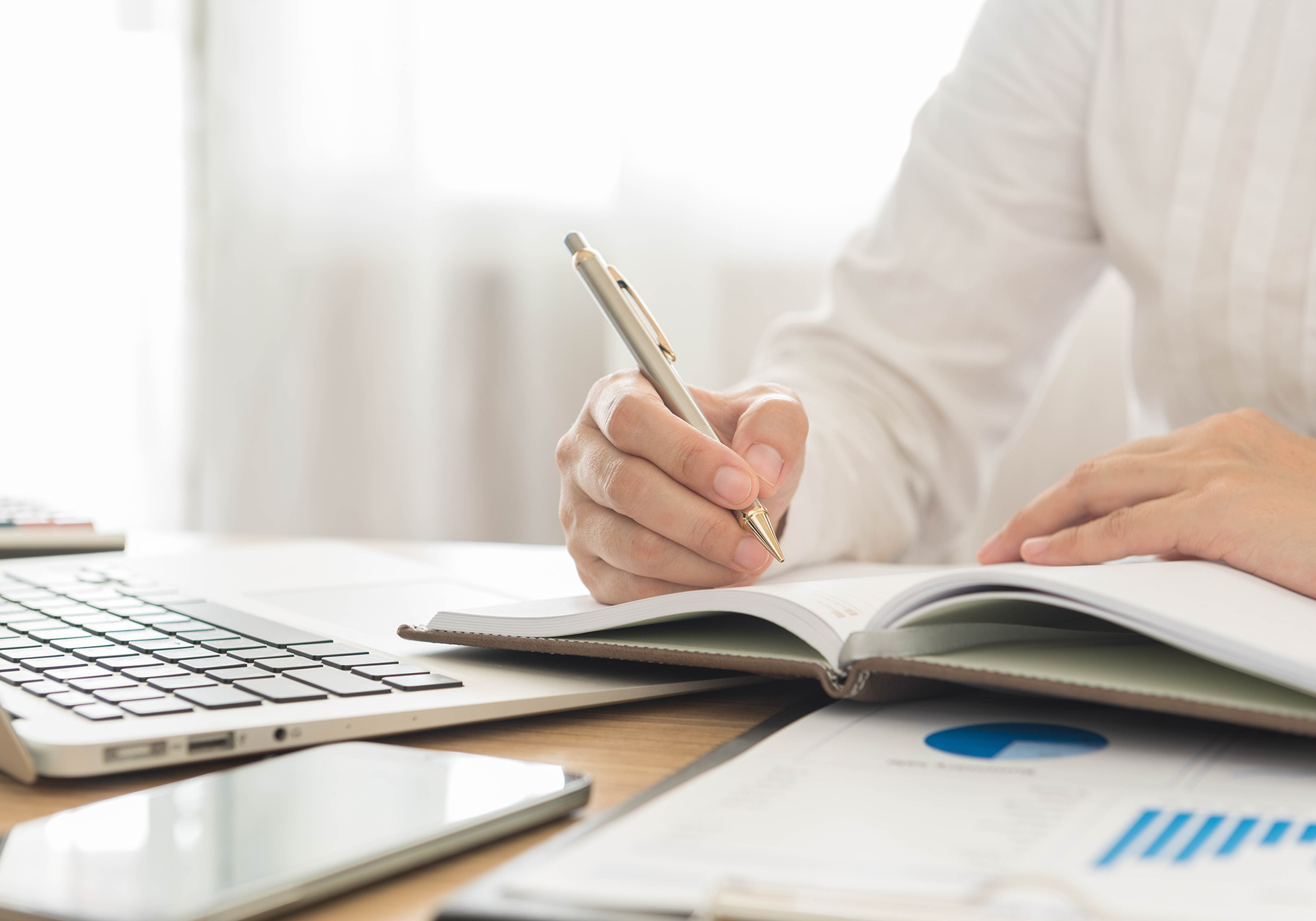 Person writing in notebook. (Image: Shutterstock)