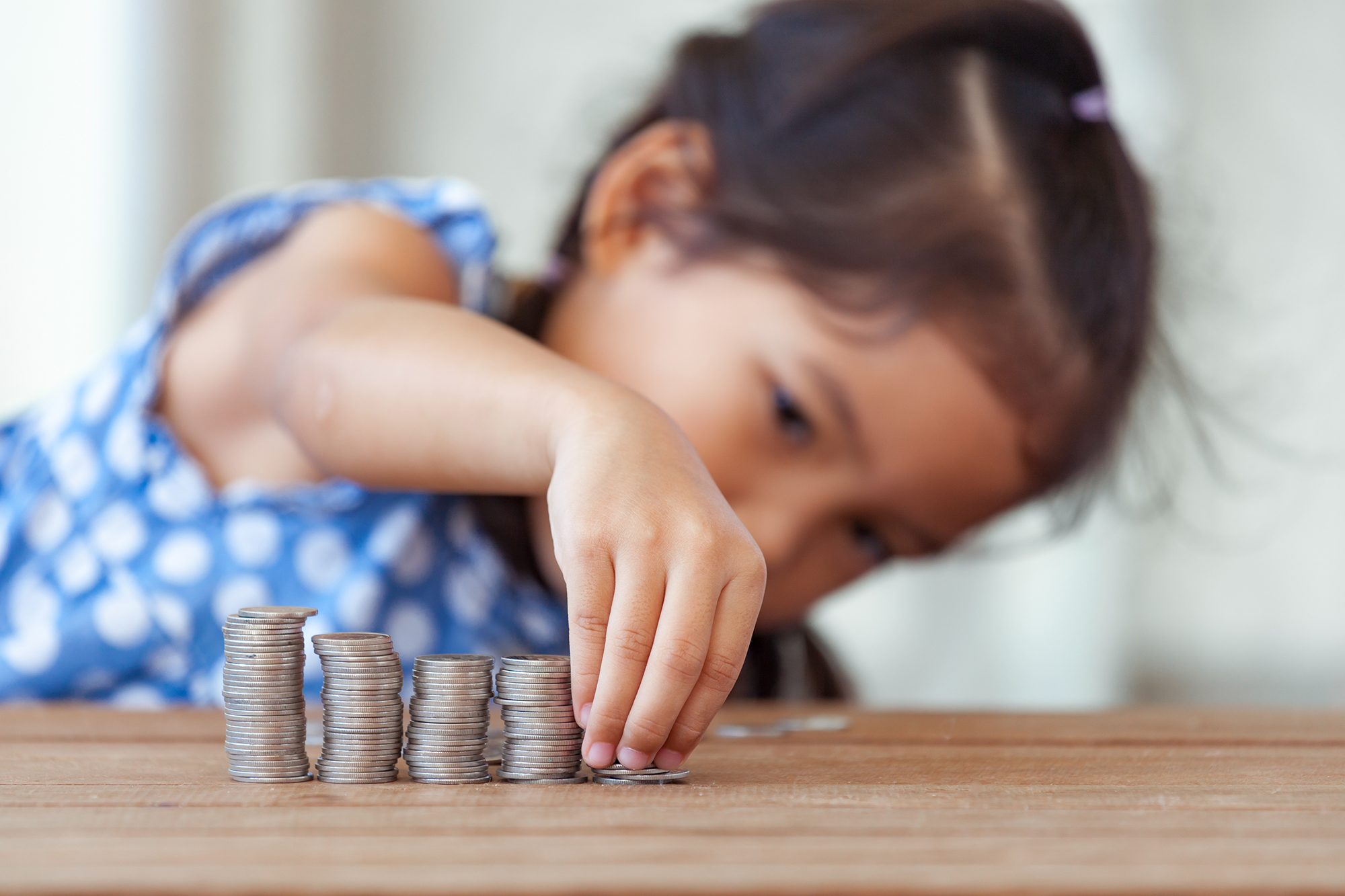 Little girl with coins. (Image: Shutterstock)