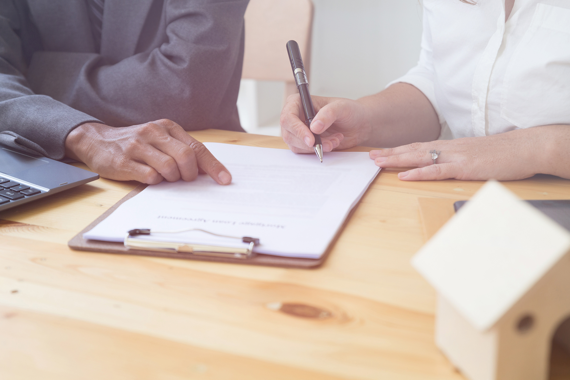 Woman signing mortgage loan agreement. (Image: Shutterstock)