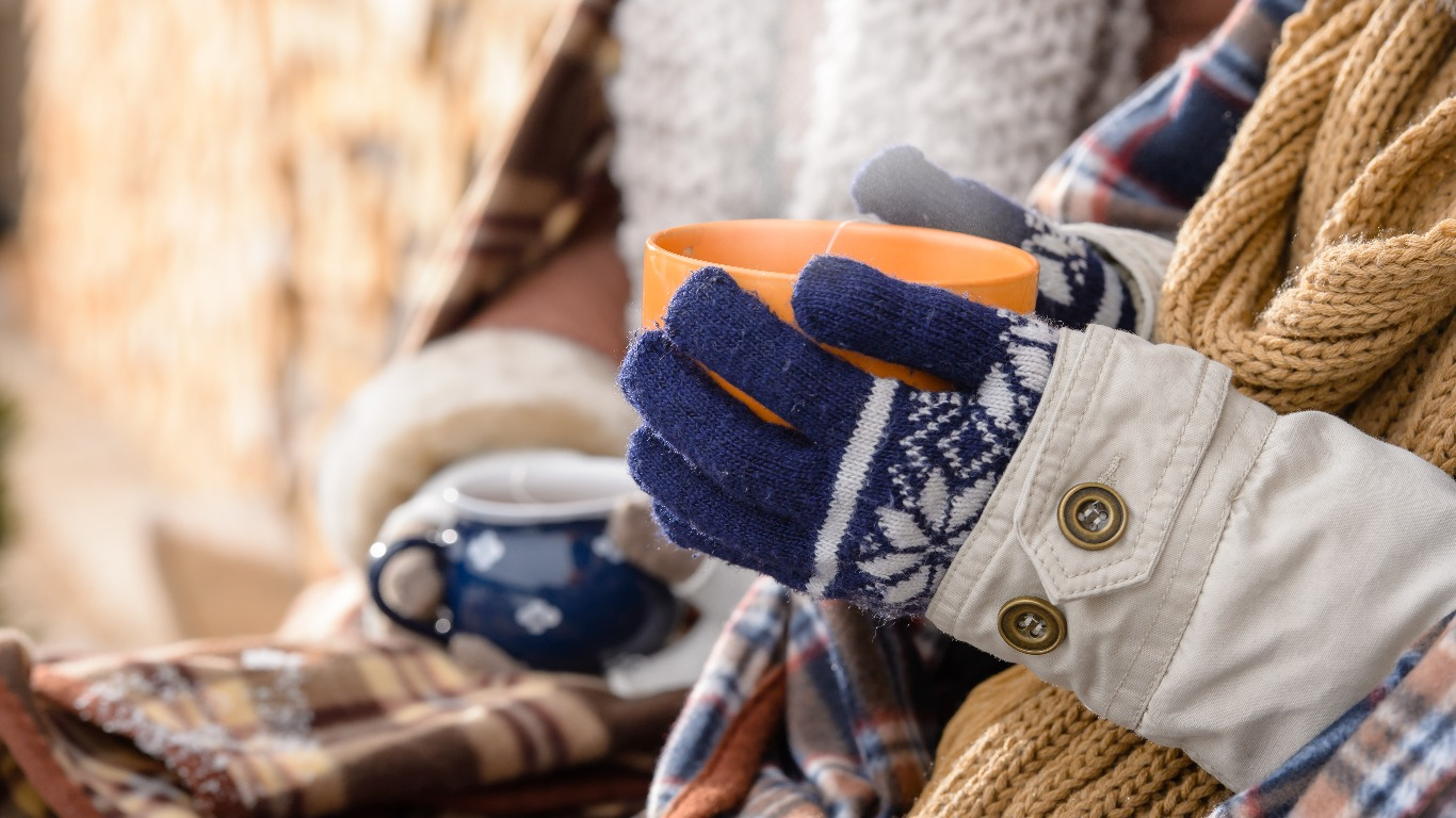 Woman wearing scarf and holding a hot drink. (Image: Shutterstock)
