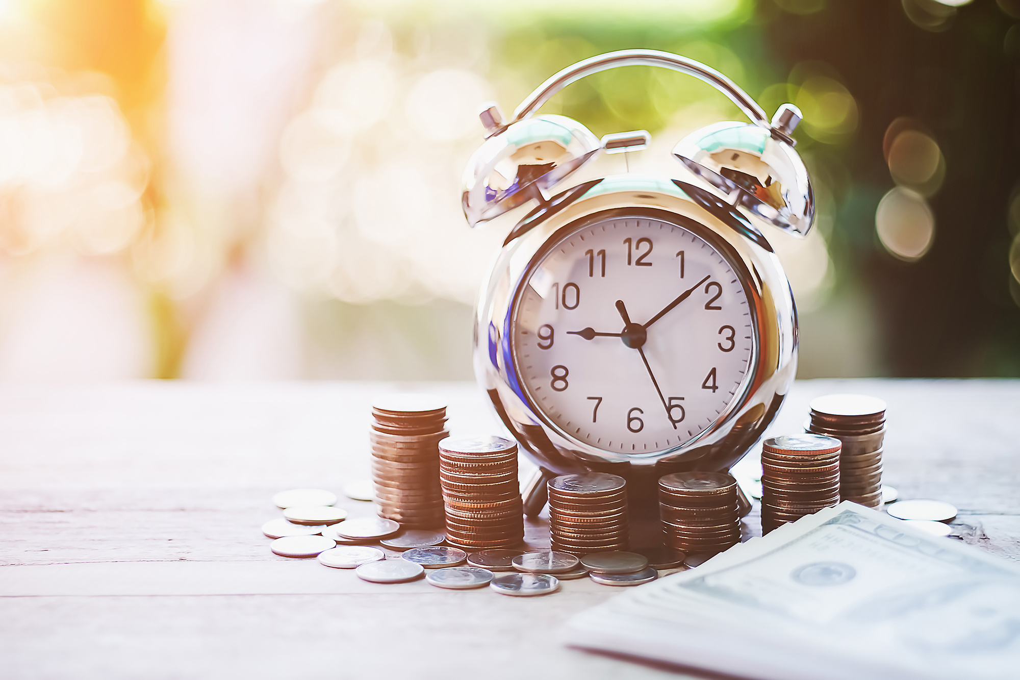 Small clock surrounded by money. (Image: Shutterstock)