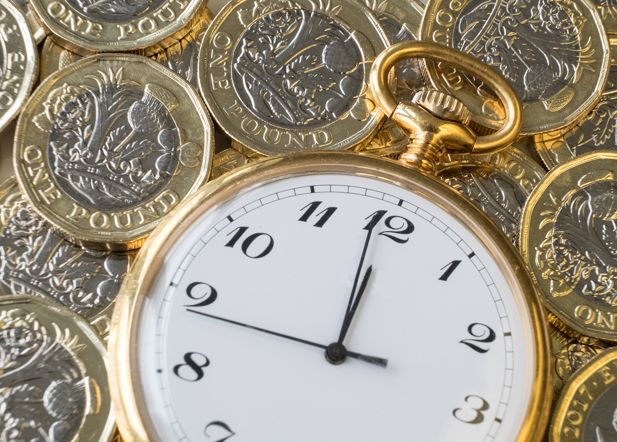 Gold watch surrounded by pound coins. (Image: Shutterstock)