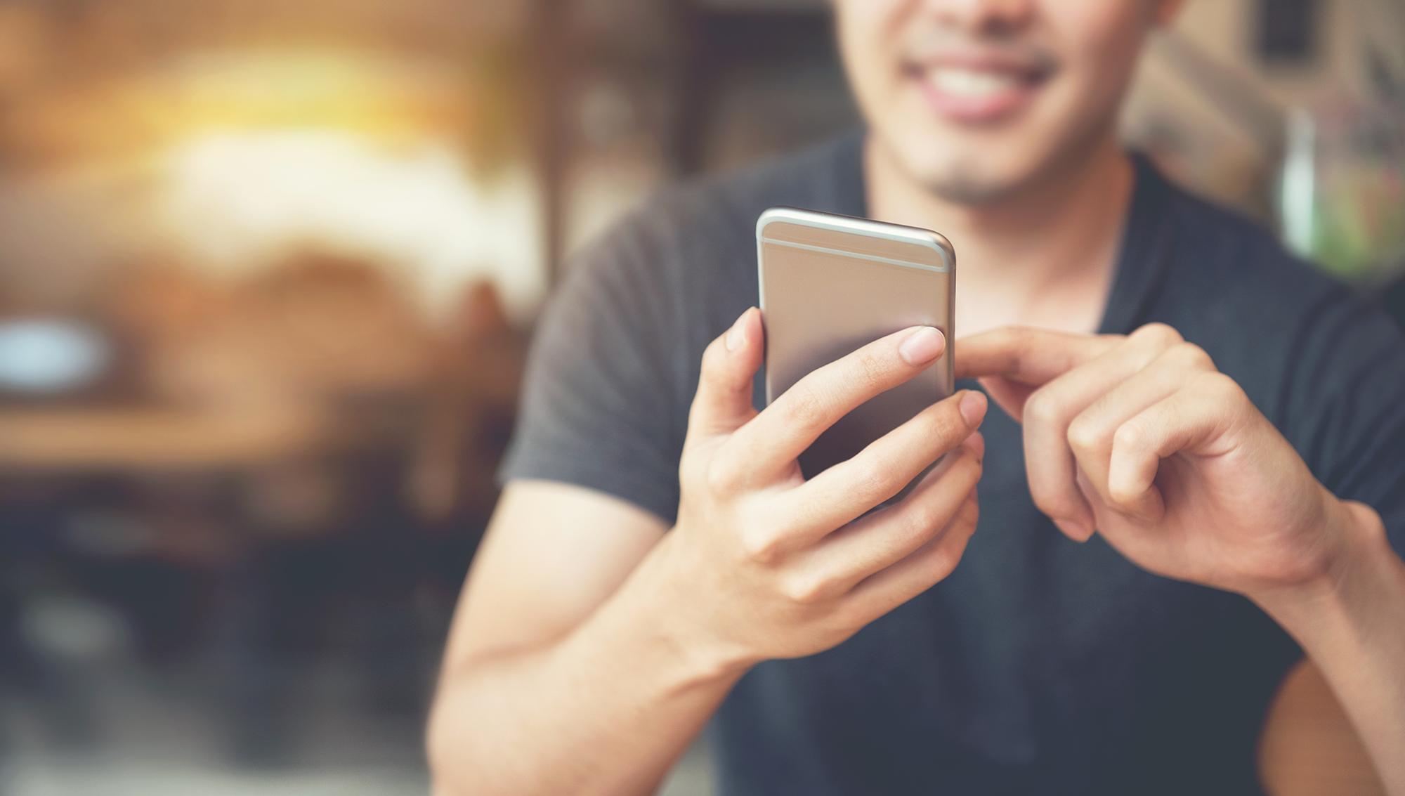 Homme utilisant un téléphone en public.  (Image: Shutterstock)