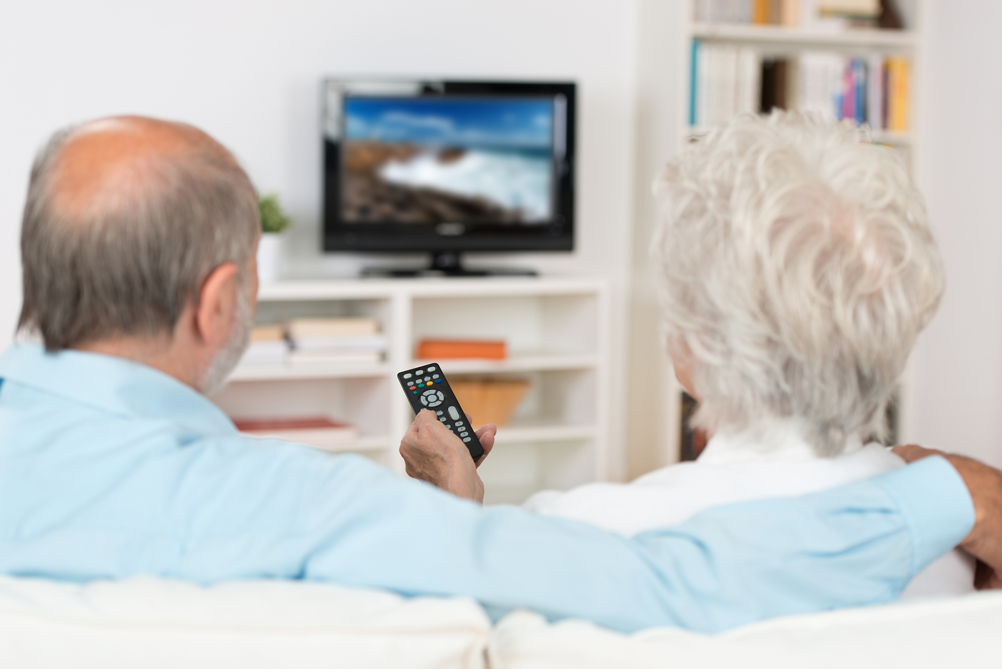 Elderly woman and man watching TV. (Image: Shutterstock)