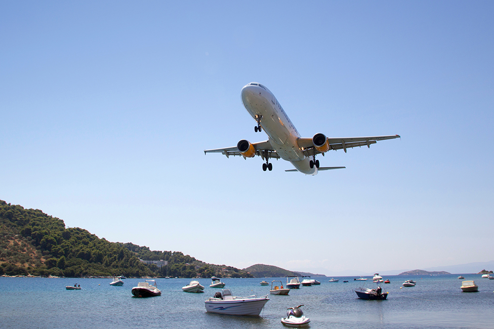 Image by Neil Lang / Shutterstock. A plane lands over the seain Greece