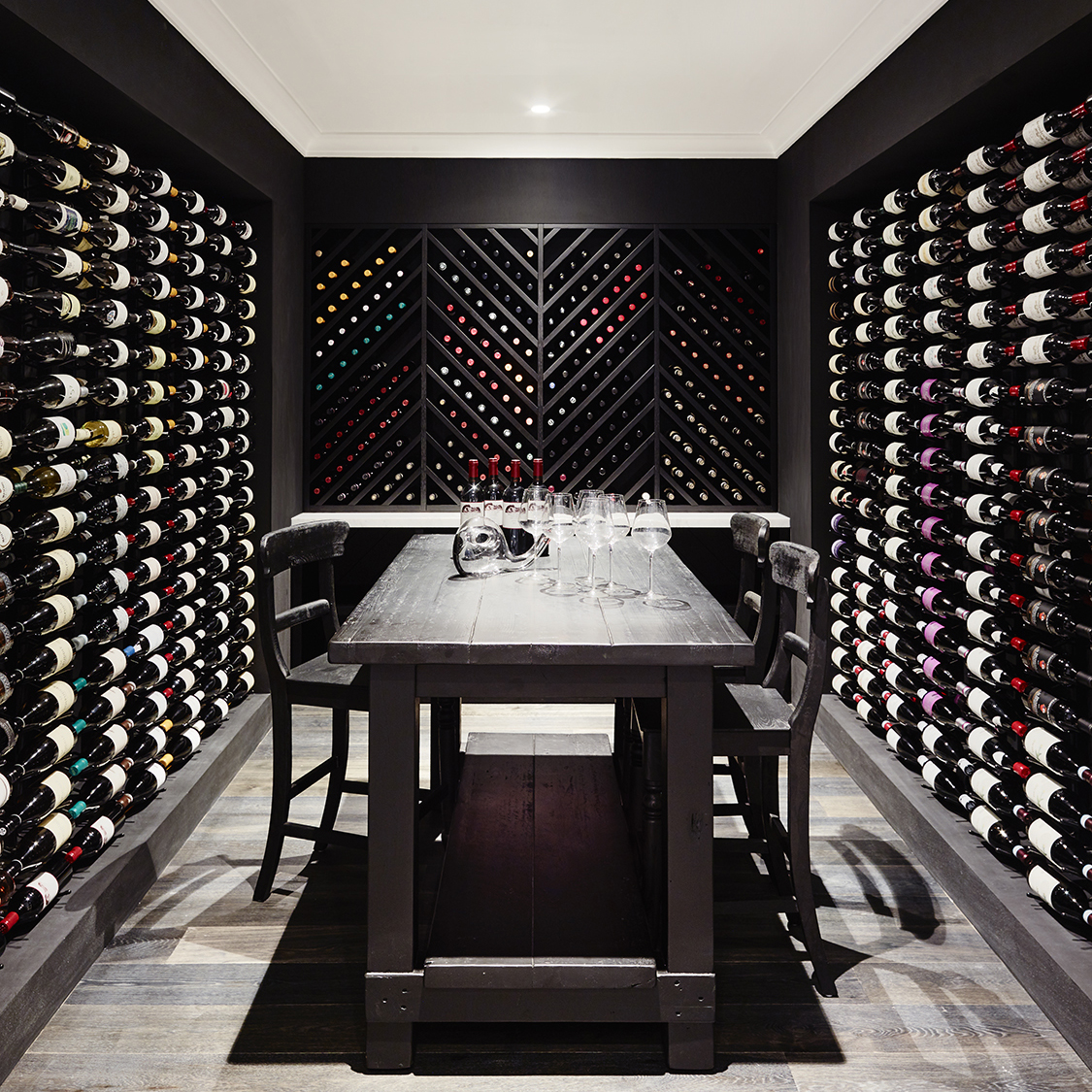 Black wine cellar with built-in wooden cabinets, designed by Greg Natale. Image: Instagram