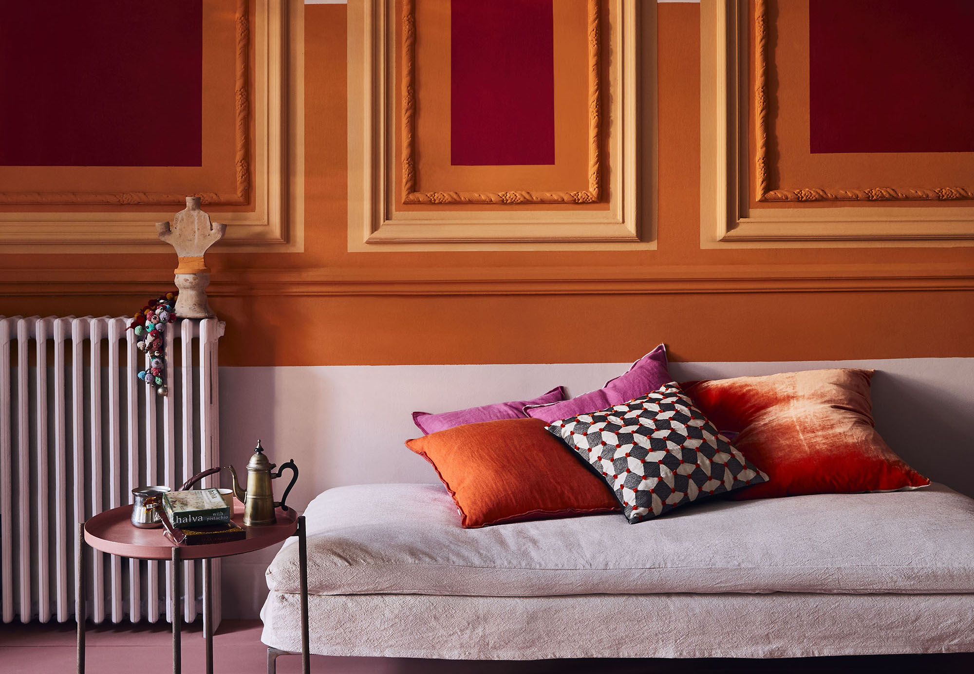 These painted panels add an antique touch to a vibrant living room scheme. Image: Annie Sloan