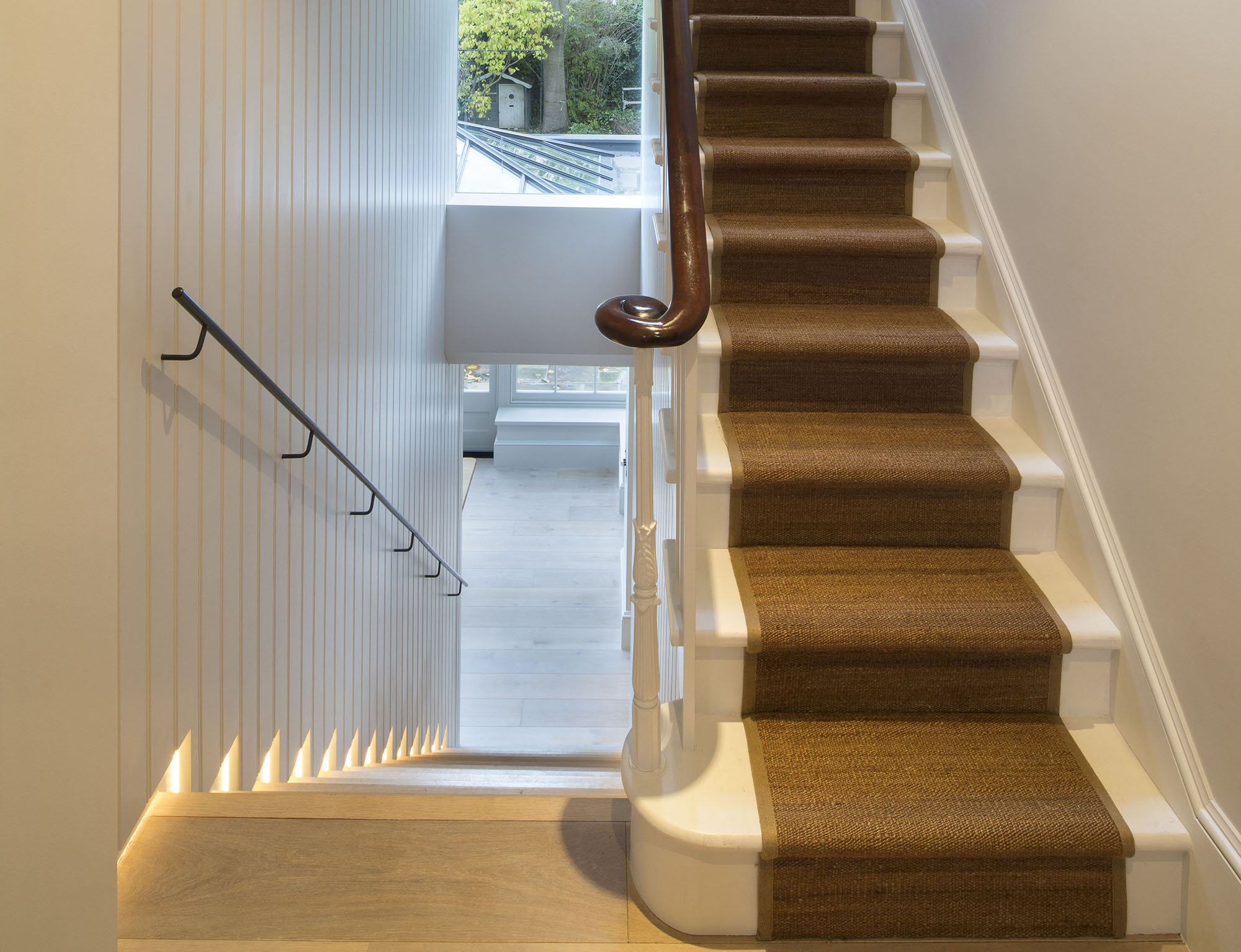 A curved banister and ornate balustrades are the stars of the show in this two-tone hallway. Image: Cousins and Cousins