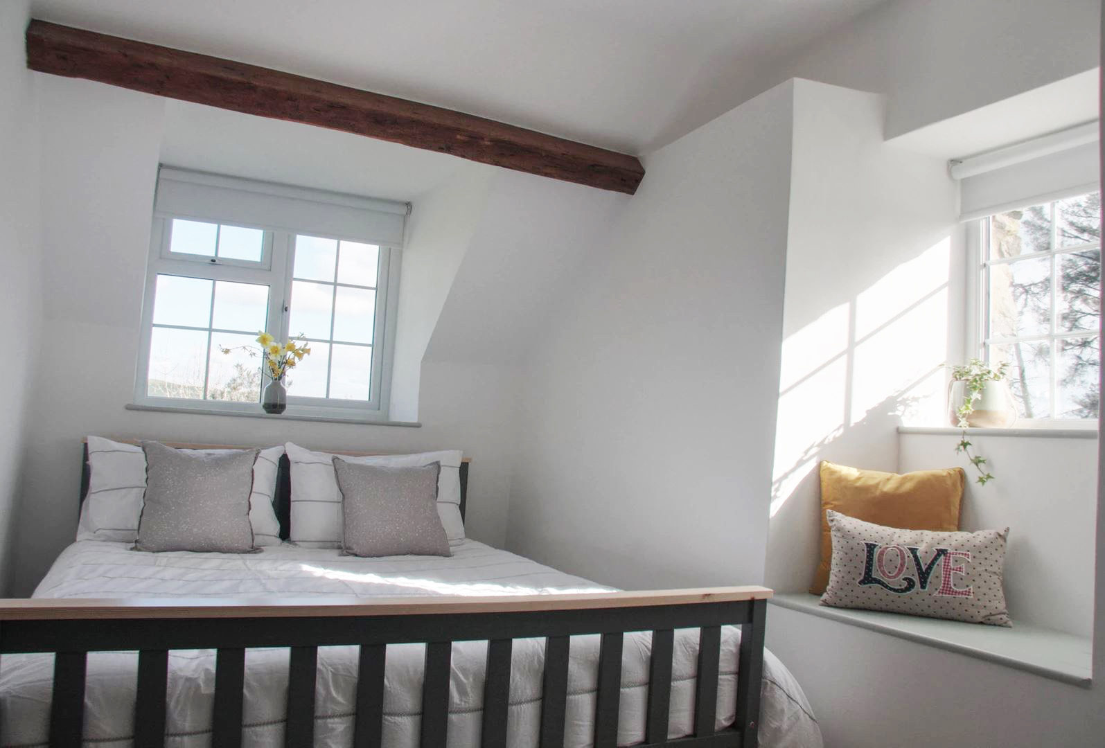 Nestled beneath the eaves, this bright bedroom is cool and cosy. Image: Cwellyn Dream